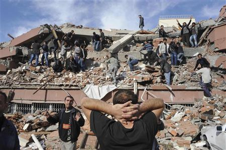 Rescue workers try to save people trapped under debris after an earthquake in Tabanli village near the eastern Turkish city of Van