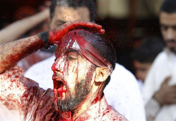 A Shi'ite Muslim shouts religious slogans as he hits himself during the Ashura mourning procession in Manama