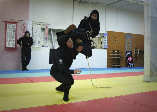 A Ninjutsu practitioner swings from a rope to attack as members of various Ninjutsu schools showcase their skills to the media in a gym at Karaj