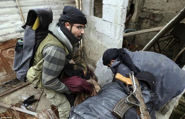 Un rebelde herido por un francotirador es apoyado por sus compañeros.