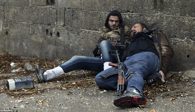 El rebelde herido con su compañero mientras se ocultan detrás de una barda.