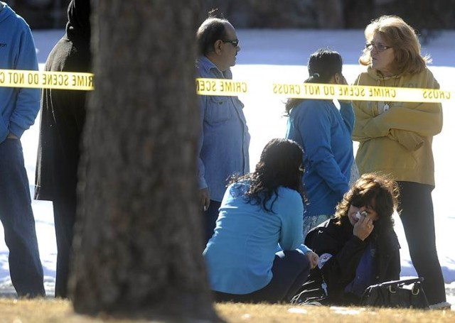 Friends and neighbors react outside a townhouse complex following an overnight hostage-taking incident in Aurora, Colorado