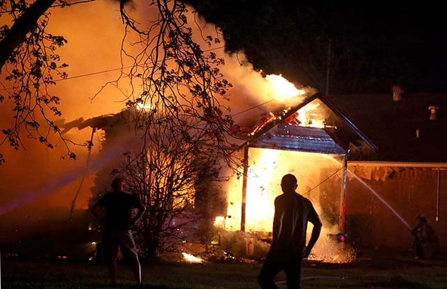 A person looks on as emergency workers fight a house fire