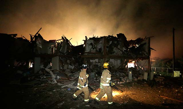 Firefighters check a destroyed apartment complex near the plant