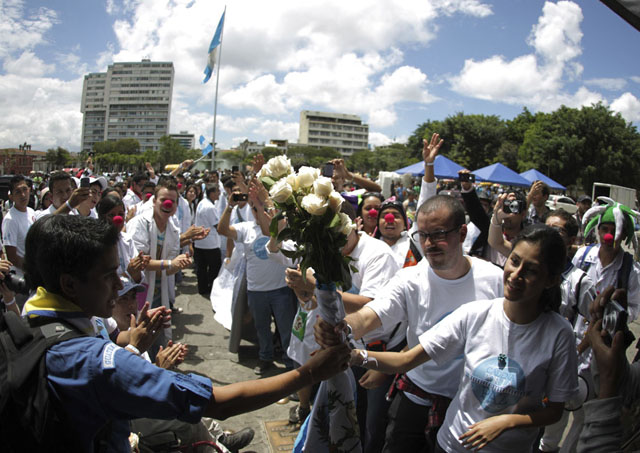 People pass bouquet of roses along human chain on streets of downtown Guatemala city to commemorate International Day of Peace in Guatemala City