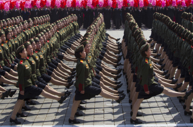North Korean soldiers march in front of flower waving civilians durin