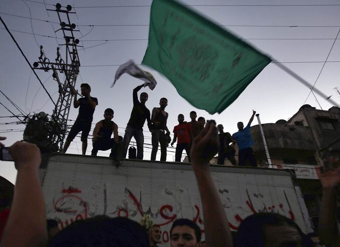 A Palestinian waves a Hamas flag as others celebrate what they said was a victory over Israel, following a ceasefire in Gaza City