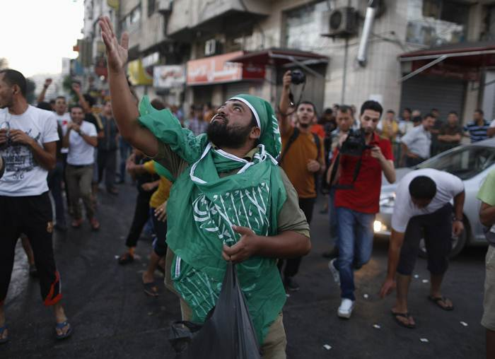 A Palestinian throws sweets as others celebrate what they said was a victory over Israel, following a ceasefire in Gaza City