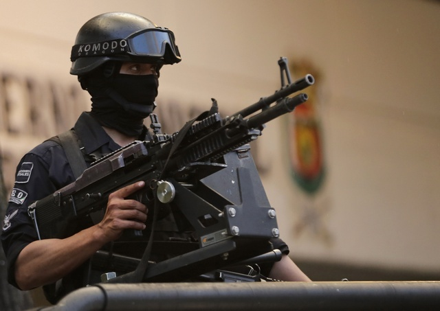 A member of the Federal Police stands guard atop a vehicle in downtown Iguala, southern Mexican state of Guerrero