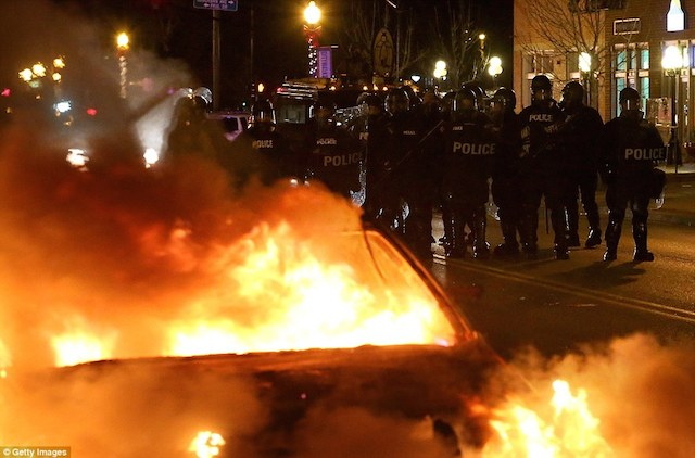237B66BC00000578-2844491-Guard_Police_officers_stand_in_a_line_next_to_a_burning_police_c-153_1416896411116