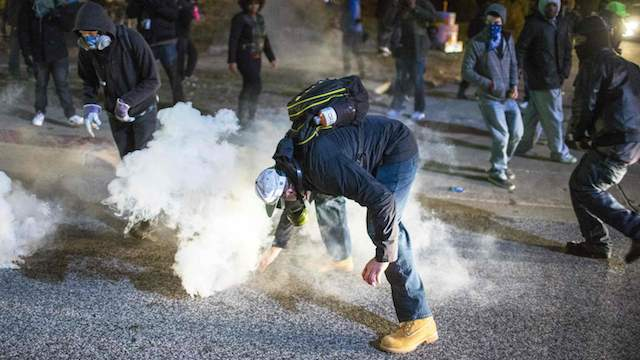 A protester reaches for a tear gas canister during a second night of protests in Ferguson, Missouri