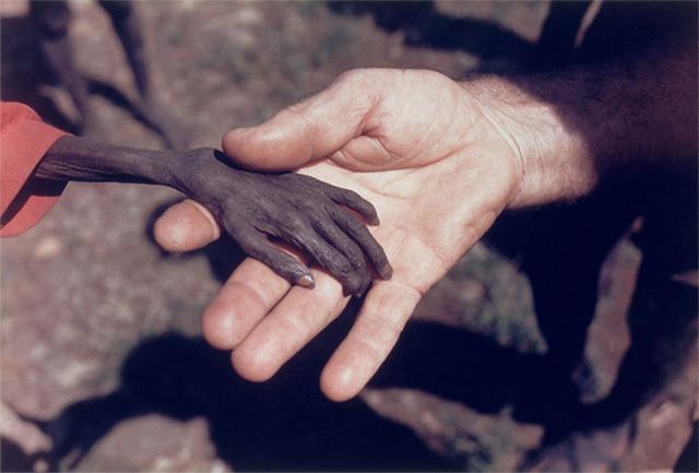 Un misionero y un niño afectado por la hambruna en Uganda (1980)