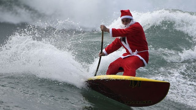 """Hombre vestido de Santa Claus participa en el concurso """"Stand Up Paddle"""""""