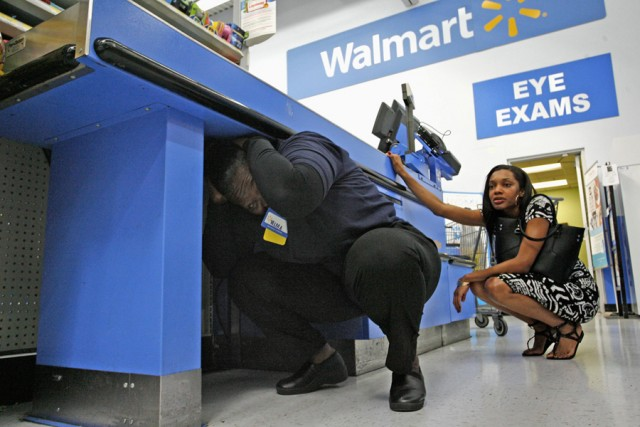 """Walmart Employee Madden crouches under checkout stand during """"Great ShakeOut"""" """" earthquake drill in Torrance, California"""