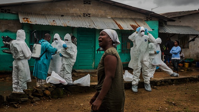 A relative grieves as a Red Cross burial team prepares to remove the body of Ofori Gweah, who died of Ebola's telltale symptoms, in a riverside area called Rock Spring Valley in central Monrovia, Liberia.