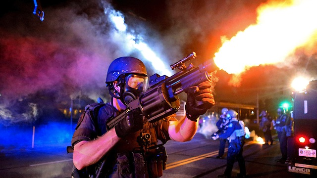 A member of the St. Louis County Police tactical team fires tear gas into a crowd of people in response to a series of gunshots fired at police during demonstrations in Ferguson, Missouri
