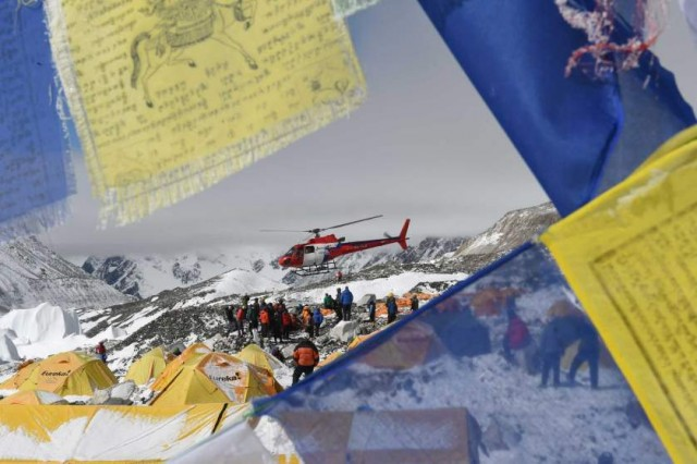 TOPSHOTS Prayer flags frame a rescue helicopter as it ferries the injured from Everest Base Camp on April 26, 2015, a day after an avalanche triggered by an earthquake devastated the camp.  Rescuers in Nepal are searching frantically for survivors of a huge quake on April 25, that killed nearly 2,000, digging through rubble in the devastated capital Kathmandu and airlifting victims of an avalanche at Everest base camp. AFP PHOTO/ROBERTO SCHMIDTROBERTO SCHMIDT/AFP/Getty Images
