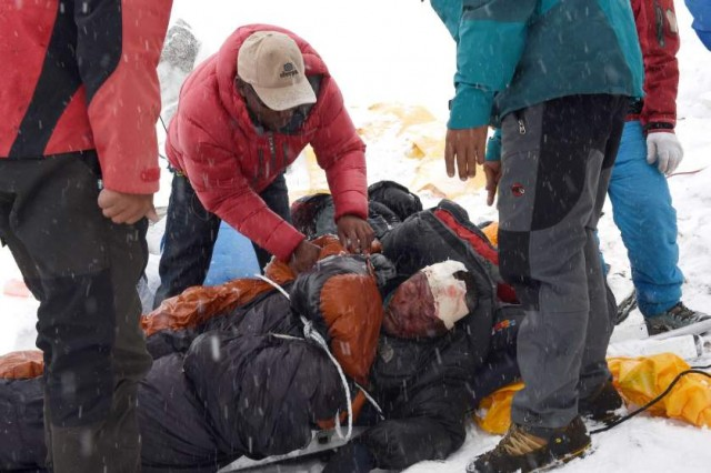 In this photograph taken on April 25, 2015, rescuers tend to a sherpa injured by an avalanche that flattened parts of Everest Base Camp.   Rescuers in Nepal are searching frantically for survivors of a huge quake on April 25, that killed nearly 2,000, digging through rubble in the devastated capital Kathmandu and airlifting victims of an avalanche at Everest base camp.   AFP PHOTO/Roberto SCHMIDTROBERTO SCHMIDT/AFP/Getty Images