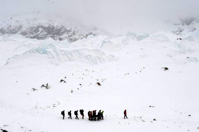 In this photograph taken on April 25, 2015, rescuers carry a sherpa injured by an avalanche that flattened parts of Everest Base Camp.   Rescuers in Nepal are searching frantically for survivors of a huge quake on April 25, that killed nearly 2,000, digging through rubble in the devastated capital Kathmandu and airlifting victims of an avalanche at Everest base camp.   AFP PHOTO/Roberto SCHMIDTROBERTO SCHMIDT/AFP/Getty Images