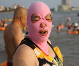 "Mandatory Credit: Photo by Imaginechina/REX (4077976h) A woman wearing a facekini Women balaclava style face masks at a beach, Qingdao, Shandong Province, China - 14 Aug 2014 Swimmers in the eastern Chinese city of Qingdao have already made waves on the Internet for their bizarre swimming gear: colorful, full-face masks. Dubbed ""facekini,"" the fabric masks cover a swimmer's entire head and neck down to the collar bones. Holes are cut for eyes, nostrils and mouth. A facekini woman says that the mask not only helps her from getting tanned, it also prevents jellyfish."