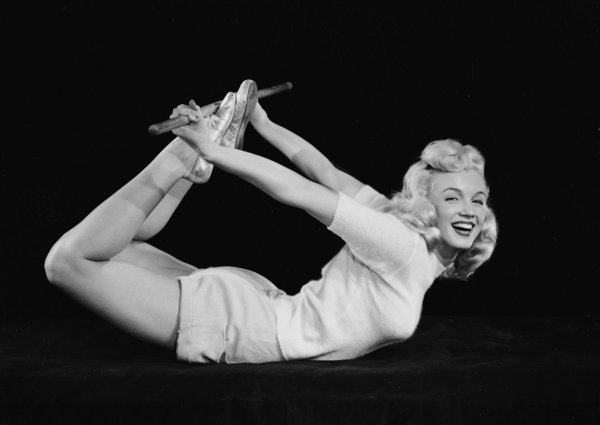 1948:  American film star Marilyn Monroe (1926 - 1962) curls herself into a bow shape and assumes a yogic exercise position.  (Photo via John Kobal Foundation/Getty Images)