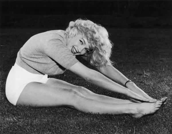 circa 1956:  American actor Marilyn Monroe (1926  - 1962) sits on the grass with her legs outstretched, touching her toes.  (Photo by Dave Cicero/Hulton Archive/Getty Images)