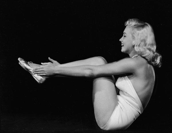 1948:  American film star Marilyn Monroe (1926 - 1962) assumes a yogic exercise position.  (Photo via John Kobal Foundation/Getty Images)