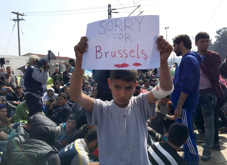 """A refugee boy holds up placard reading """"Sorry for Brussels"""" as refugees and migrants take part in a protest against the closure of the border at Greek-Macedonian"""