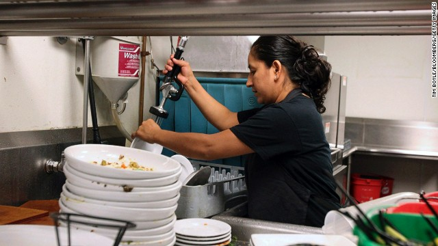A dishwasher rinses plates at Bar Louie restaurant in the River North neighborhood of Chicago, Illinois, U.S., on Saturday, July 20, 2013. Bar Louie's newest dishwashers, cooks and servers owe their jobs to U.S. consumers who are spending more on dining, amusement parks and other close-to-home activities. Photographer: Tim Boyle/Bloomberg via Getty Images