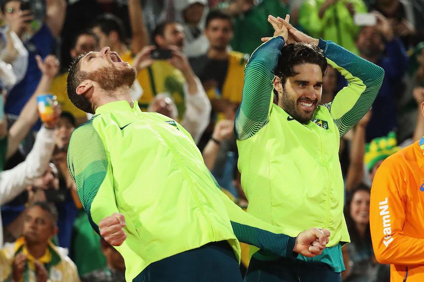 Alison Cerutti y Bruno Schmidt al momento de recibir su medalla de oro por la prueba de voleibol