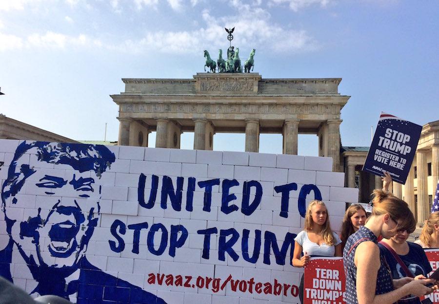 Activistas derriban un muro de cartón en Alemania e invitan a los estadounidenses que viven en ese país a votar en contra de Trump