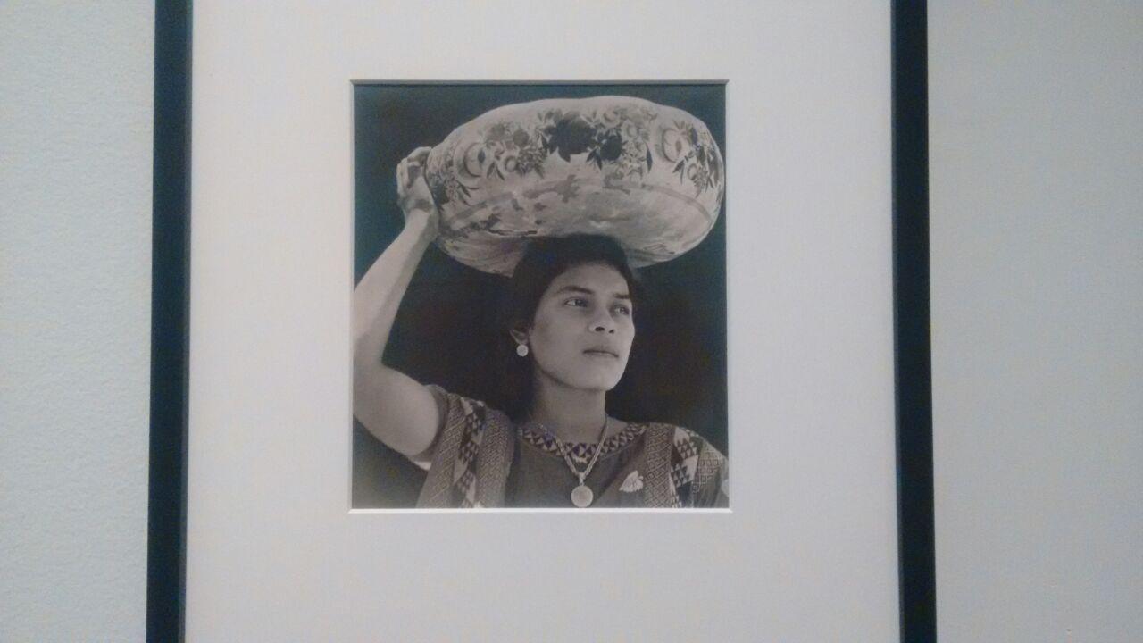 Fotografía de mujer con una jícara de barro en la cabeza.