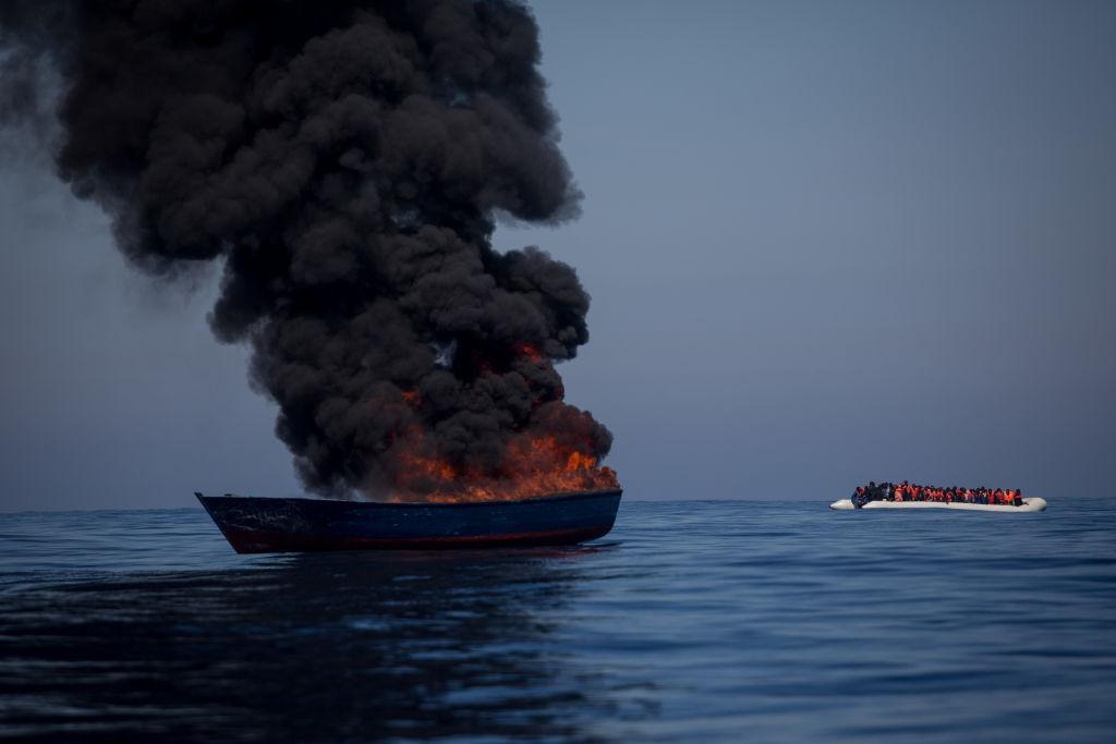 barco incendiado con migrantes en una lancha al fondo