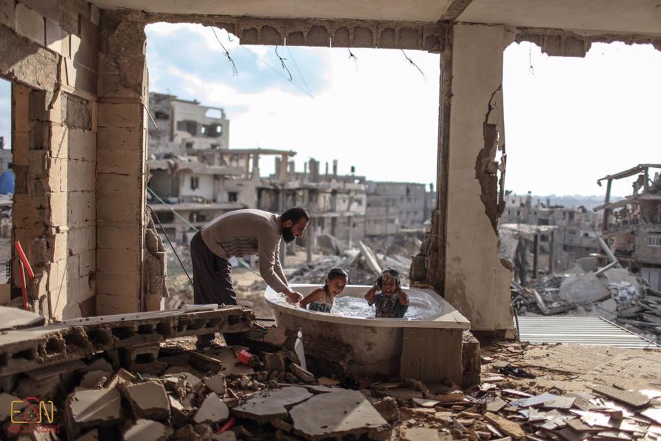 niños tomando un baño de tina en medio de ruinas de Gaza